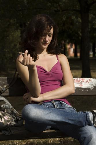 Young woman smoking marijuana outdoor on park bench
